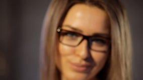 Nadenkende verdachte blonde vrouw die zware ontworpen zwarte glazen dragen die de camera bekijken stock video