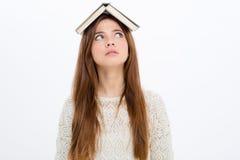 Nadenkende vermakelijke jonge vrouw met boek op haar hoofd Stock Afbeeldingen
