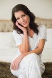 Nadenkende vrij bruine haired vrouwenzitting op een bed Stock Afbeeldingen