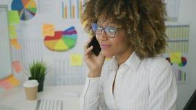Nadenkende vrouw in bureau die op telefoon spreken stock video