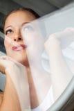 Nadenkende Vrouw die door Glasdeur kijkt royalty-vrije stock foto's