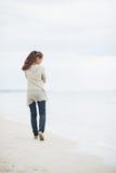 Nadenkende vrouw die in sweater op strand lopen stock foto