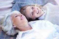 Nadenkende vrouw die van picknick met oude moeder in het park genieten Stock Foto's