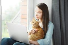 Nadenkende vrouw gelezen informatie die over notitieboekje rode pussy kat houden Royalty-vrije Stock Afbeelding