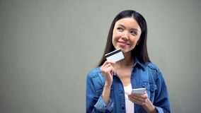Nadenkende vrouw met smartphone en creditcard die over online aankoop denken stock foto's