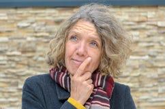 Nadenkende vrouw op middelbare leeftijd met hand aan kin stock fotografie
