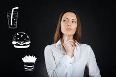 Nadenkende vrouw wat betreft haar kin terwijl het kiezen van voedsel in een koffie stock afbeeldingen