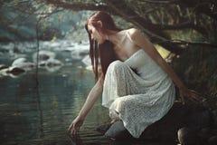 Nadenkende vrouw wat betreft stroomwateren Royalty-vrije Stock Afbeelding
