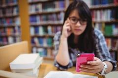 Nadenkende vrouwelijke student die een mobiele telefoon met behulp van Royalty-vrije Stock Afbeelding
