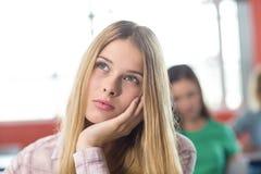 Nadenkende vrouwelijke student in klaslokaal Stock Foto's