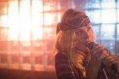 Nadenkende vrouwelijke zanger die in nachtclub presteren stock afbeelding