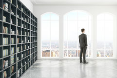 Nadenkende zakenman in bibliotheekkant Stock Foto's