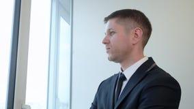 Nadenkende zakenman die de afstand van het venster onderzoeken stock video