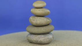 Naderend de piramide van stenen wordt gemaakt die zich op het zand bevinden dat Geïsoleerde stock footage