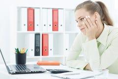 Nadgodzinowy pojęcie: zanudzający młody żeński urzędnik siedzi przy jej spojrzeniami przy ekranem komputerowym i biurkiem Zdjęcia Royalty Free