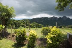 Nadi, Fiji. Lush mountain landscape with green rainforest, plants and fencing under a stormy sky in Port Denarau, Fiji Royalty Free Stock Image