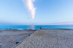 Nadmorski widok krystaliczny błękitne wody morze, piaskowata plaża i groyne falochron przy błękitną godziną pod, majestatycznym b obraz stock