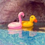 Nadmuchiwany różowy flaming i żółta kaczka bawimy się w basenie zdjęcie royalty free