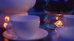 Nadruk die van theekopje op theepot met kaars onder het verschuiven voor het verwarmen op lijst in caffee stock video