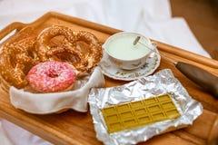 Nadruk op cappuccinator en antieke porseleinkop groene chocolade met matchathee, en pretzels met bevroren donuts stock foto's