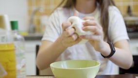 Nadruk op de handen die van het tienermeisje en wit pluizig slijm drukken uitrekken stock video