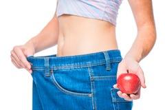 Nadruk op een appel in slanke meisjes` s hand tegen een slank lichaam Royalty-vrije Stock Afbeelding