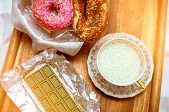 Nadruk op groene chocolade met de Chinese matchathee, antieke porseleinkop met slagroom en pretzels met bevroren donuts royalty-vrije stock afbeeldingen