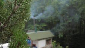 Nadruk op Pijnboomtak Vaag Huis van de Pijp die een Dikke Rook is stock footage