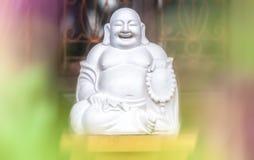 Wit standbeeld van zittende en lachende vette monnik. Stock Foto's