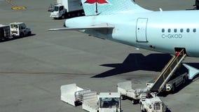 Nadruk van arbeider het schikken van passagiersbagage aan Air Canada-vliegtuigen stock footage