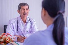 Nadruk van Aziatische rijpe mannelijke arts en vrouwelijke geduldige zitting die in het ziekenhuis spreken royalty-vrije stock afbeelding