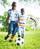 Nadruk van de Chldren de speelvoetbal op de bal Stock Foto's