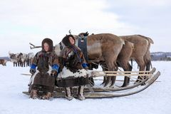 Children of the indigenous people of the Yamal Peninsula sitting. NADYM, RUSSIA — MARCH 04, 2018: Two boys Nenets during the traditional holiday of the stock photography