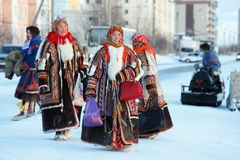 Nenets women in bright national fur garments walking around the. NADYM, RUSSIA - MARCH 04, 2018: Nenets women in bright traditional fur garments malitsa Royalty Free Stock Images