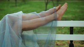 Nadzy cieki dziewczyna w błękit spódnicie która kłama na ławce i rusza się palec u nogi durin fotografii sesi zdjęcie wideo