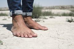 Nadzy cieki mężczyzna na krakingowej suchej ziemi Obraz Stock