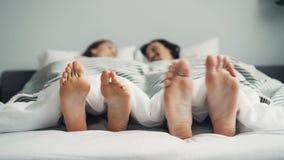 Nadzy cieki samiec i kobiety chodzenie w łóżku pod koc w śmiesznym tanu zbiory