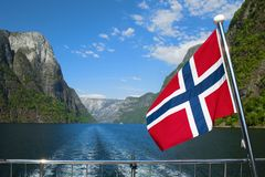 Naeroyfjord and a national flag during the breathtaking Norwegian Aurlandsfjord and Naeroyfjord cruise royalty free stock image