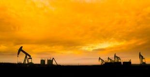 Nafciane pompy przy polem naftowym z zmierzchu nieba tłem obrazy royalty free