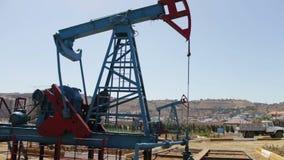 Nafciani pumpjacks w pracującym polu naftowym w Baku, Azerbejdżan Sylwetka pracować nafcianą pompę na tle niebieskie niebo i zbiory