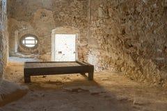 Nafplio, Griekenland, 28 December 2015 Oude gevangeniscel bij Palamidi-kasteel in Griekenland met een houten bed Stock Afbeelding