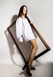 Naga dziewczyna w mężczyzna ` s białego koszulowego mienia drewnianej ramie Obraz Stock