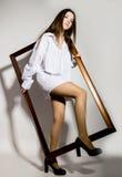 Naga dziewczyna w mężczyzna ` s białego koszulowego mienia drewnianej ramie Obrazy Royalty Free