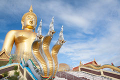 Naga and large gold buddha statue under construction in Thai temple with clear sky.WAT MUANG, Ang Thong, THAILAND. Stock Photos
