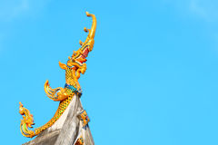 Naga statue on blue sky background. Naga statue atop the temple Royalty Free Stock Image