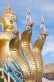 Naga y estatua grande de Buda del oro bajo construcción en templo tailandés con el cielo claro WAT MUANG, Ang Thong, TAILANDIA imágenes de archivo libres de regalías