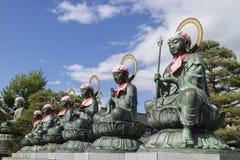 Nagano - Japão, o 3 de junho de 2017: Seis estátuas de bronze da Buda com vermelho Fotografia de Stock