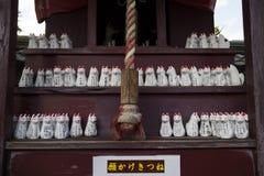Nagano - Japan,June 3, 2017: Row of small votive Kitsune, fox fi. Gurines, animal guardians in front of an Inari Shrine Royalty Free Stock Image