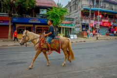 NAGARKOT,尼泊尔2017年10月04日:骑在dowtown的未认出的男孩一匹马在城市在Nagarkot尼泊尔 库存图片
