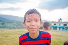NAGARKOT, NEPAL 11 DE OUTUBRO DE 2017: Rapaz pequeno brincalhão não identificado que olha a câmera nos utdoors na vila de Nagarko Fotos de Stock Royalty Free